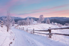 Winter country landscape with timber fence and snowy road Royalty Free Stock Image