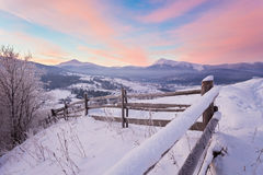 Winter country landscape with timber fence and snowy road Stock Photos