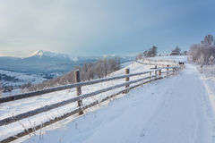 Winter country landscape with timber fence and snowy road Stock Photography