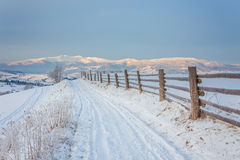 Winter country landscape with timber fence and snowy road Royalty Free Stock Photo