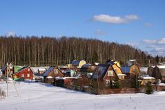 Winter in country side. Colorful houses of a small village in forest, winter Stock Photos