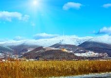 Winter country sunshiny mountain Ukraine. Country sunshiny landscape with field and mountain with new-fallen snow  Zakarpattia Oblast, Ukraine Royalty Free Stock Photos