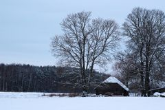 Winter countryside view with house and trees stock photography