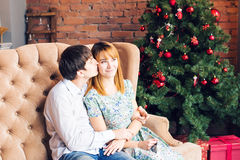 Winter, couple, christmas and people concept - smiling man and woman hugging over x-mas tree background stock photos