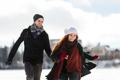 Cheerful young couple playing in snowy mountains. Winter couple running over the snow in mountains Royalty Free Stock Photos