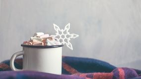 Winter cozy concept. Coffee with marshmallows and decorative shiny snowflake in white enameled metal cup in purple warm wool scarf. Warm weekend in cold stock photo