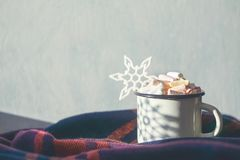 Winter cozy concept. Coffee with marshmallows and decorative shiny snowflake in white enameled metal cup in purple warm wool scarf. Warm weekend in cold royalty free stock photo
