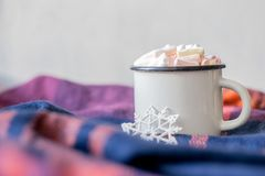 Winter cozy concept. Coffee with marshmallows and decorative shiny snowflake in white enameled metal cup in purple warm wool scarf royalty free stock image