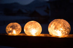 Winter craft: Ice lanterns with flickering fire of a candle. Ice lanterns with flickering fire of a candle on the railing of a wooden house in the mountains royalty free stock photos
