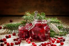 Winter cranberry sauce in glass jars with fresh cranberries, dec. Orated fir branches and snow on the old wooden background, selective focus stock photo