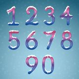 Winter cream numbers set with snow caps. Frozen New year digits. With snowflakes on it kit. Icicles numbers on dark snowy background Royalty Free Stock Image