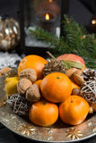 Winter cristmas fruits and nuts on silver plate. With christmas decoration Royalty Free Stock Images
