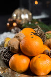 Winter cristmas fruits and nuts on silver plate. With christmas decoration Royalty Free Stock Photography