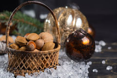 Winter cristmas nuts is wicked basket on white ice. Winter cristmas nuts in wicked basket with christmas decoration Stock Photography