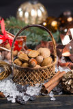 Winter cristmas nuts is wicked basket on white ice. Winter cristmas nuts in wicked basket with christmas decoration Stock Image