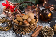 Winter cristmas nuts is wicked basket on white ice. Winter cristmas nuts in wicked basket with christmas decoration Royalty Free Stock Photos