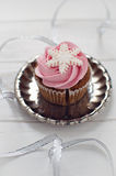 Winter cupcake. Pink winter cupcake with snowflake and silver ribbon Stock Photo