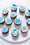 Winter cupcakes with fondant flower decorations. Delicate and elegant wedding chocolate cupcakes with white frosting and fondant decorations Royalty Free Stock Image