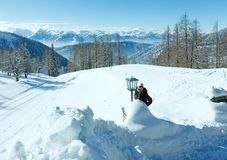 Winter Dachstein mountain massif and woman near the lamp. Stock Photography