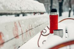 Winter Date Ideas for Couples. Winter holidays, hot drinks concept. thermos and cups on a snowy bench in winter park. Winter Date Ideas for Couples. Winter stock photography