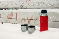 Winter Date Ideas for Couples. Winter holidays, hot drinks concept. thermos and cups on a snowy bench in winter park. Winter Date Ideas for Couples. Winter royalty free stock photo
