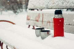 Winter Date Ideas for Couples. Winter holidays, hot drinks concept. Red thermos and cups on a snowy bench in winter park. Winter Date Ideas for Couples. Winter royalty free stock photography