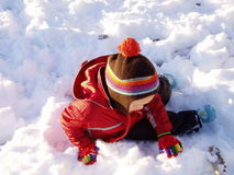 Winter Day. Young child is playing in a pile of snow in the late afternoon Stock Images