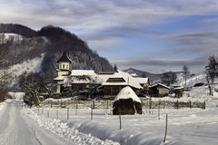 Winter day in a county near mountains. Snow, church, road in the background royalty free stock photos
