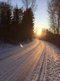 Winter day. Curvy road and sunset. Royalty Free Stock Photography