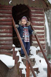 Winter day on a playground. Little girl in winter clothes playing outside on cloudy day Stock Photos