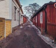 Narrow street with old wooden houses Raasepori Tammisaari Finland. Winter day in Raasepori Tammisaari with old wooden houses in a narrow street with melting snow Stock Photos