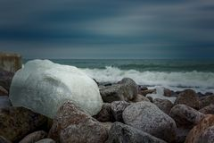Winter day by the sea. The sky is cloudy. Sea waves are striking the shore. Ice on the rocks Royalty Free Stock Photography