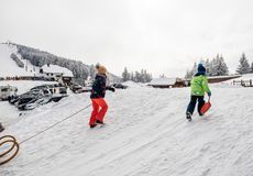 Winter day with snow and happy kids climbing the sledding slope Stock Images