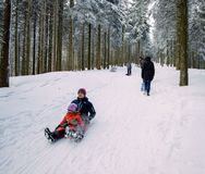 Winter day with snow and happy mother and doughter sleighing the Stock Photography