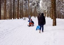 Winter day with snow and happy mother and doughter sleighing the Royalty Free Stock Photos