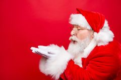 Winter December sale discount black friday. Profile side view ag. Ed Santa in costume blow on open palms hand near face pouted lips isolated on shine red royalty free stock images