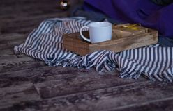 Winter decor: cup of coffee, a gift, a tray, a ball and a cozy striped plaid. Selected focus. Winter decor: white cup of coffee, a gift, a tray, awhite ball and stock image