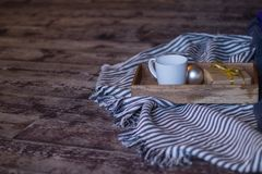 Winter decor: cup of coffee, a gift, a tray, a ball and a cozy striped plaid. Winter decor: white cup of coffee, a gift, a tray, awhite ball and a cozy striped stock image