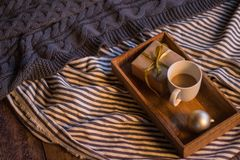 Winter decor: cup of coffee, a gift, a tray, a ball and a cozy striped plaid. Winter decor: white cup of coffee, a gift, a tray, awhite ball and a cozy striped stock photos
