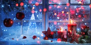 Winter Decoration With Candles Near The Snow-Covered Window Stock Photos