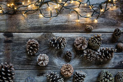 Winter decorative light on rustic wooden timbers with fir cones Royalty Free Stock Photography