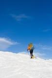 Winter, der in den Bergen auf Schneeschuhen mit einem Rucksack und einem Zelt wandert Lizenzfreie Stockfotos
