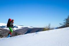 Winter, der in den Bergen auf Schneeschuhen mit einem Rucksack und einem Zelt wandert Stockfotografie
