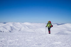 Winter, der in den Bergen auf Schneeschuhen mit einem Rucksack und einem Zelt wandert Stockbilder