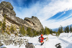 Winter, der in den Bergen mit einem Rucksack und Schneeschuhen wandert Lizenzfreie Stockbilder