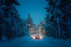 Winter, der nachts - Lichter des Autos in der schneebedeckten Straße fährt Lizenzfreie Stockfotografie