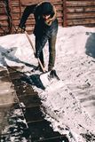 Winter details - man cleaning snow in courtyard. Caucasian male using snow shovel. Winter details - young man cleaning snow in courtyard. Caucasian male using royalty free stock photography