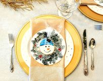 Winter Dinner Table Setting with Snowman. A winter dinner table setting with plates, fork, knife, spoon, silverware, wine glasses and a snowman cookie in the royalty free stock photography