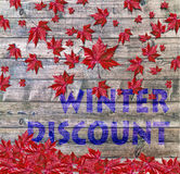 Winter Discount and red falling leaves laying on wooden background Royalty Free Stock Photos