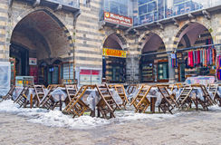 The winter in Diyarbakir. DIYARBAKIR, TURKEY - JANUARY 15, 2015: The tables and chairs of the outdoor cafe in the courtyard of former Hasan Pasha Inn are covered Stock Photography